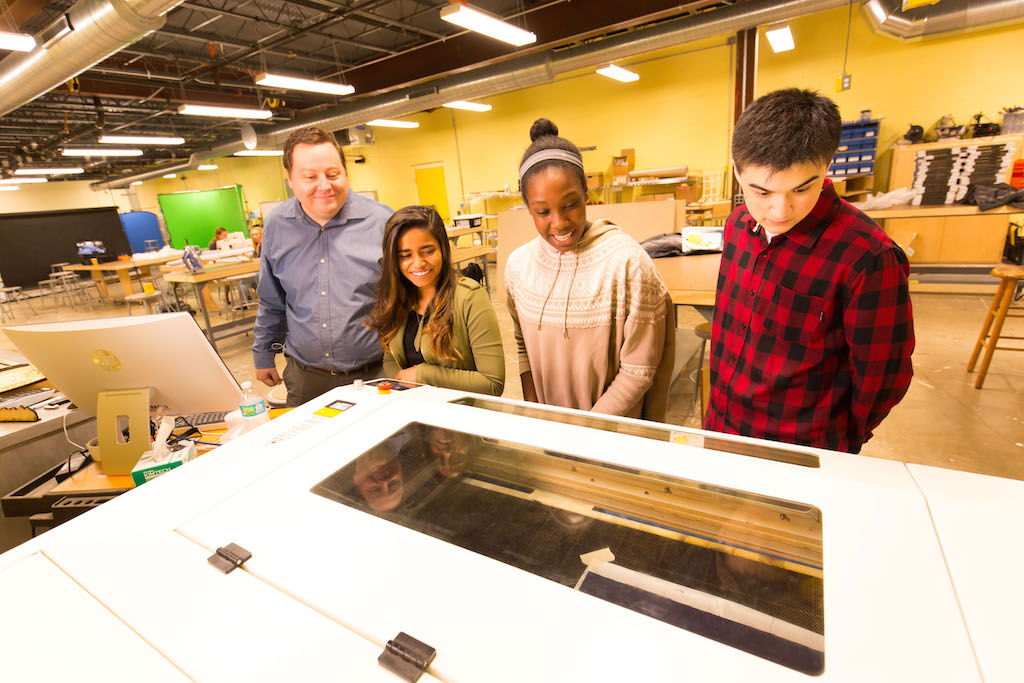 Kilbane (left) and students watch the laser cutter in action